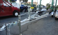 Picture of Tandem Axle Boat Trailer on Concrete. Red Van in the background.