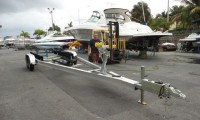 Picture of Tandem Axle Boat Trailer on Concrete. Boat in the background.